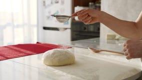 Pasta d'impastamento del panettiere in farina sulla tavola Chiuda su delle mani femminili che funzionano con la pasta stock footage
