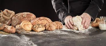 Pasta d'impastamento del panettiere per produrre pane gastronomico fotografia stock