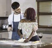 Pasta de amasamiento de los pares felices de la raza mixta junto en cocina Imagenes de archivo