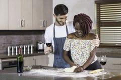 Pasta de amasamiento de los pares felices de la raza mixta junto en cocina Fotos de archivo libres de regalías