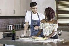 Pasta de amasamiento de los pares felices de la raza mixta junto en cocina Imagen de archivo