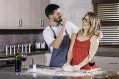 Pasta de amasamiento de los pares felices junto en cocina Imagenes de archivo