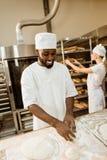 pasta de amasamiento del panadero afroamericano en la fabricación que cuece mientras que su trabajo del colega borrosa foto de archivo