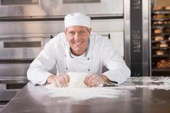 Pasta de amasamiento sonriente del panadero en contador imagenes de archivo