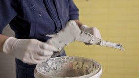 Pasta de ganho da massa de vidraceiro da moça de uma cubeta em uma espátula Reparo home vídeos de arquivo