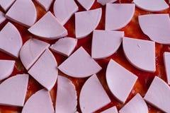 pasta de la pizza manchada con la salsa de tomate y con las rebanadas de salchicha como fondo fotos de archivo libres de regalías
