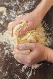 Pasta de mezcla con las manos Foto de archivo