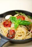 Pasta degli spaghetti con i pomodori ciliegia al forno ed il basilico Immagine Stock