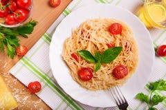 Pasta degli spaghetti con i pomodori ed il prezzemolo sulla tavola Fotografia Stock Libera da Diritti