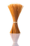 Pasta degli spaghetti del grano intero di Brown su fondo bianco isolato Fotografia Stock Libera da Diritti