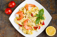 Pasta del Fettuccine in salsa crema con i gamberetti di re su un piatto la tavola di legno Vista superiore Fotografie Stock