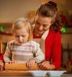 Pasta del rodillo de la madre y del bebé en cocina de la Navidad Imagenes de archivo
