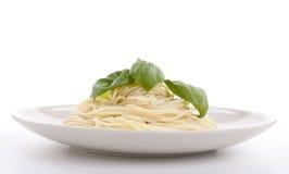 Pasta deliziosa fresca con basilico isolato su bianco Fotografia Stock