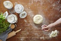 Pasta della spolverata della mano con la superficie di legno della cucina della farina Fotografia Stock