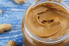 Pasta di arachidi su un fondo di legno fotografia stock libera da diritti