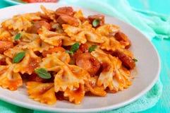 Pasta di Farfalle con i bei pezzi della salsiccia in salsa al pomodoro Immagini Stock