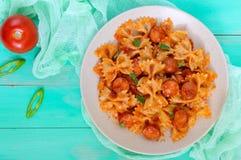 Pasta di Farfalle con i bei pezzi della salsiccia in salsa al pomodoro su un fondo luminoso Immagine Stock