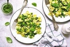 Pasta di Farfalle con la salsa di pesto, i piselli e lo zucchini la cima rivaleggia immagini stock libere da diritti