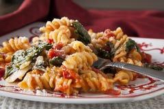 Pasta di Fusilli con i pomodori e gli spinaci freschi del bambino Immagine Stock