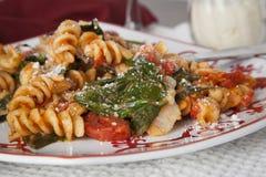 Pasta di Fusilli con i pomodori e gli spinaci freschi del bambino Fotografie Stock