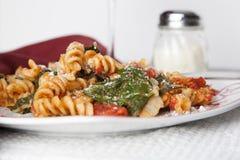 Pasta di Fusilli con i pomodori e gli spinaci freschi del bambino Fotografia Stock