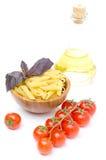 Pasta di Penne, pomodori freschi, basilico, olio d'oliva isolato su bianco Fotografia Stock