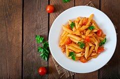 Pasta di Penne in salsa al pomodoro con il pollo, pomodori decorati con prezzemolo Fotografia Stock Libera da Diritti