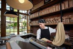 Pasta di rotolamento della donna in caffè immagine stock
