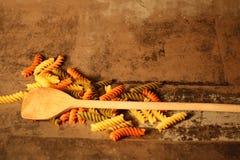 Pasta di tricromia con la cottura del cucchiaio su fondo di pietra fotografie stock libere da diritti