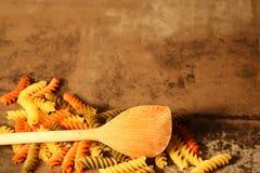 Pasta di tricromia con la cottura del cucchiaio su fondo di pietra fotografie stock
