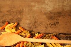 Pasta di tricromia con la cottura del cucchiaio su fondo di pietra fotografia stock libera da diritti