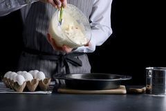 Pasta di versamento dell'uomo per la torta dolce che fa concetto fotografia stock