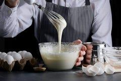 Pasta di versamento dell'uomo per la torta dolce che fa concetto fotografie stock libere da diritti