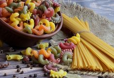 Pasta of different colors, spaghetti, black pepper and bay leaf lie on the table. royalty free stock photo