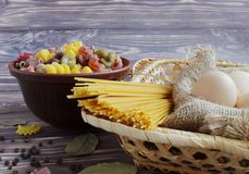 Pasta of different colors, spaghetti, three eggs, black pepper and bay leaf on a dark background and bamboo basket. Pasta of different colors, spaghetti for stock images