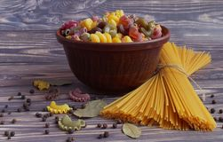 Pasta of different colors, spaghetti lying on the table, on a dark background. Pasta of different colors, spaghetti for cooking stock image