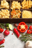Pasta with different vegetables, spices and herbs in wooden boxe Royalty Free Stock Images