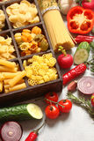 Pasta with different vegetables, spices and herbs in wooden boxe Stock Photography