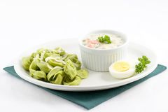 Pasta and dill sauce. Spinach tortellini filled with cheese and a side of savory dill sauce filled with corn,carrots,and peas, add an egg slice and parsley as royalty free stock photography