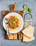 Pasta dinner. Spaghetti Bolognese in metal plate on rustic wooden board with Parmesan cheese, grater and fresh basil Royalty Free Stock Images