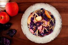 Pasta dish with apples, purple cabbage and bacon, above scene. On wooden background Stock Photo