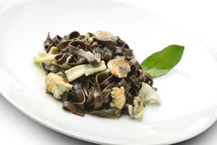 Pasta Dish Chocolate Fettuccine with Prawns and Cuttlefish. In white plate Stock Photo