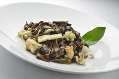 Pasta Dish Chocolate Fettuccine with Prawns and Cuttlefish  2. Pasta Dish Chocolate Fettuccine with Prawns and Cuttlefish in white plate Stock Images