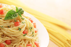 Pasta dish with copy space. Sideways shot of a pasta dish with dry spaghetti in the background Stock Images