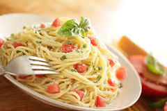Pasta dish with ingredients. Meatless pasta dish with fresh tomatoes and basil sprinkled with Parmesan cheese Royalty Free Stock Photo