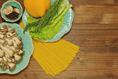 Pasta dish ingredients on blue ceramic plates. Different cooking ingridients such as spaghetti, mushrooms, salad leaves, herbs, bell pepper, garlic and so on stock image