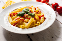 Pasta dish on the plate. Hot delicious pasta dish with sauce on white plate prepared for dinner and raw macaroni with red cherry tomatoes on the white wooden Royalty Free Stock Photo