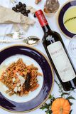Pasta Dish on Purple Plate Beside Is Robust Wine Bottle Stock Photo