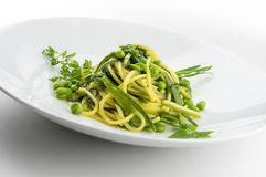 Pasta dish spaghetti with herbs and spring veggies. Isolated on white Royalty Free Stock Image