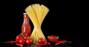 Pasta dry spaghetti with tomatoes and pepper slowly rotates.